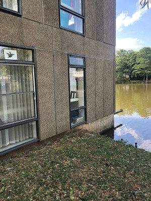 A photo of 'The Nouse Office' on Campus West. A concrete building with two rectangular windows on the edge of a lake