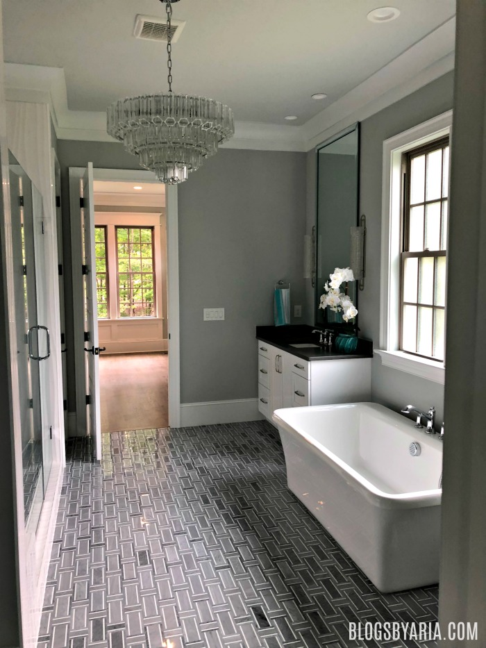 gray master bathroom with chandelier
