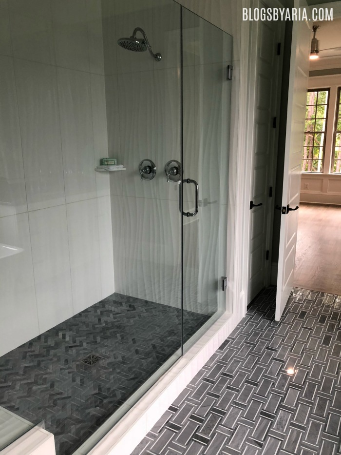 I love the gray tile flooring and the textured shower walls