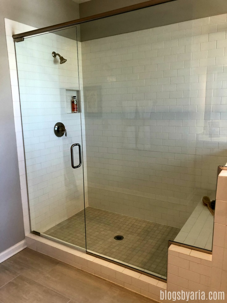 large walk-in shower with subway tile and bench