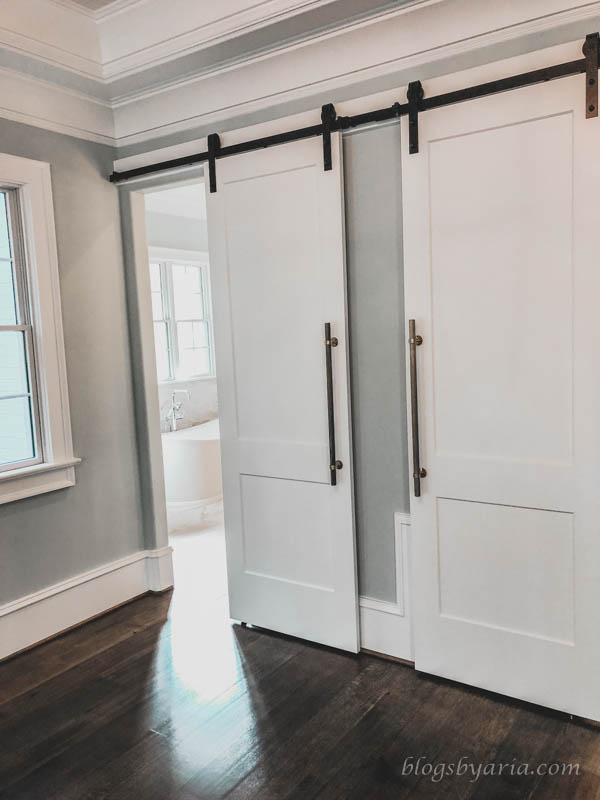 barn doors lead from the master bedroom into the his and hers en suite