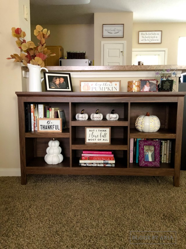 neutral pumpkins decorate this bookshelf for fall