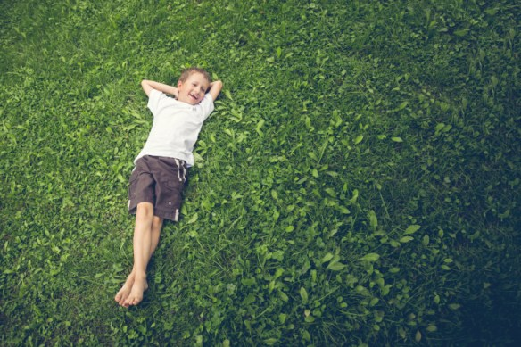 Young boy lying in the grass and laughing