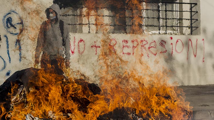 A masked Chilean protester stands behind a burning barricade in front of graffiti that reads 'no more repression'