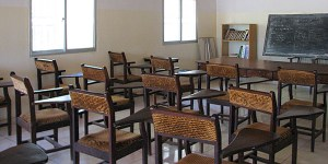 An empty classroom with desks, chairs and a blackboard