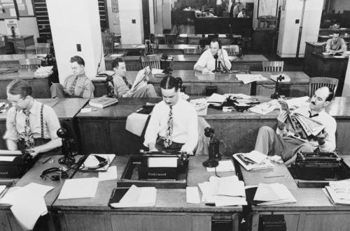 The Mercury music staff office: where men with Hitler mustaches confidently read the newspaper.