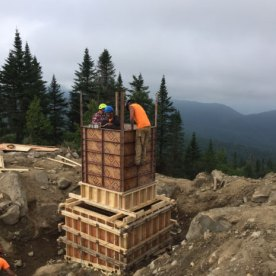 Test des ancrages en les soumettant à une forte pression. Construction du coffrage du pylône avant au terminal du sommet. Coulée de béton du pylône avant au terminal du sommet.