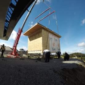 Transfert du bâtiment au moyen d'une grue. Mise en place du bâtiment sur ses fondations et positionnement des conduits électriques.