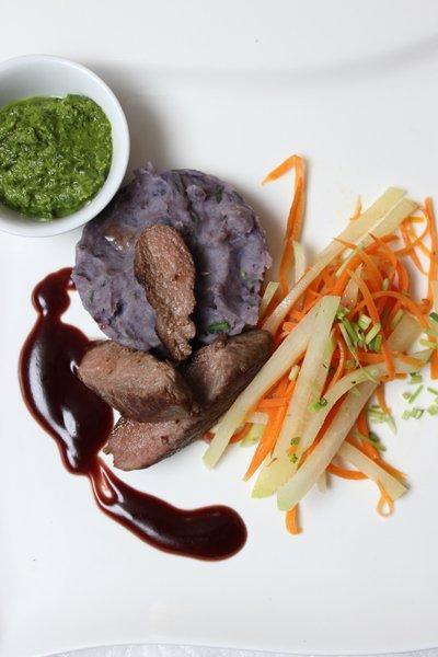 Lammlendenfilet auf lila Kartoffelstampf, Gemüsestreifen und Granatapfelsoße