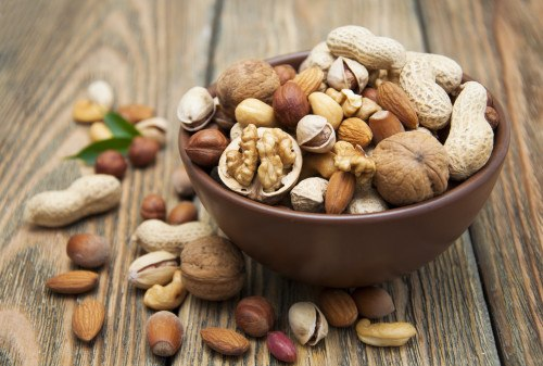 Mixed nuts in a bowl on a wooden background