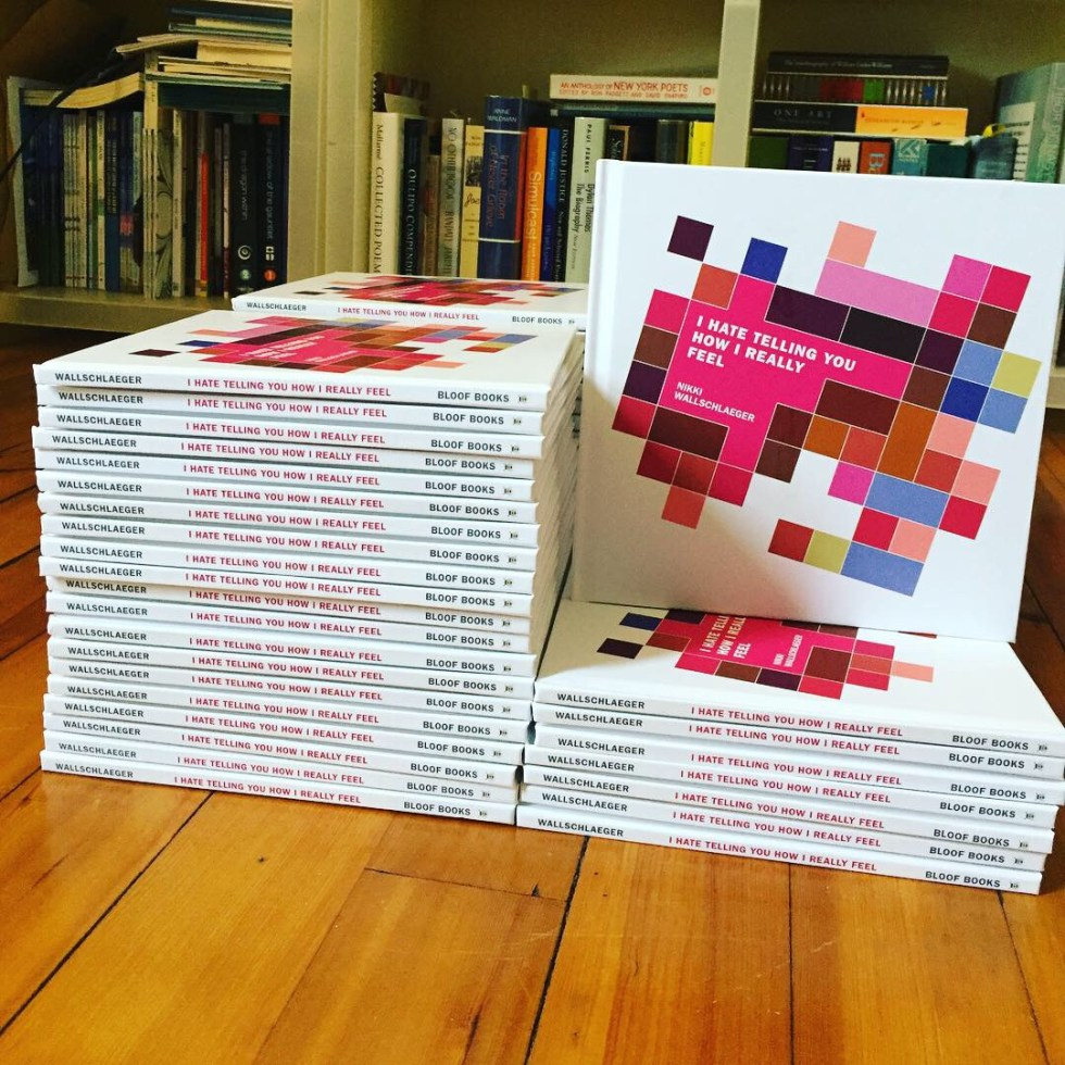 4 stacks of the book I Hate Telling You How I Really Feel by Nikki Wallschlaeger, sitting on a hardwood floor in front of a bookcase.