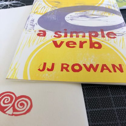 Two copies of a simple verb by JJ Rowan. The top copy reveals the hand-printed linocut cover design in yellow and lavender with red text. The bottom copy is turned to show the back, which is blank except for a red hand-carved stamp in an abstract spiral shape.