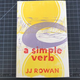 A copy of a simple verb by JJ Rowan on a black gridded cutting mat. The hand-printed linocut cover design is made up of two large yellow semicircles and a large lavender open oval, overlapping. Red lettering spells out the title and author's name.
