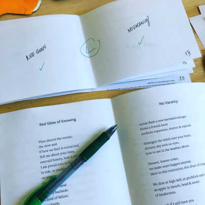 "Printed proof of Rat Queen by Katie Jean Shinkle with small hand-marked mockbook showing imposition notes. The book's two central poems can be partially seen: ""Red Glow of Knowing"" on the left page and ""No Vacancy"" on the right."
