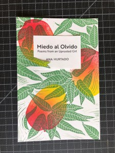 A copy of the chapbook Miedo al Olvido by Ana Hurtado, including multicolored ripe mangos and dark green leaves in a hand-printed linocut pattern, and text in black ink.