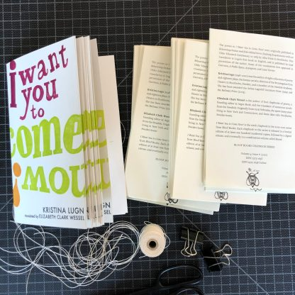 Copies of I Want You to Come Now! in progress. A stack of folded covers and a stack of folded interiors sit side by side on a black gridded cutting mat, with thread and binder clips