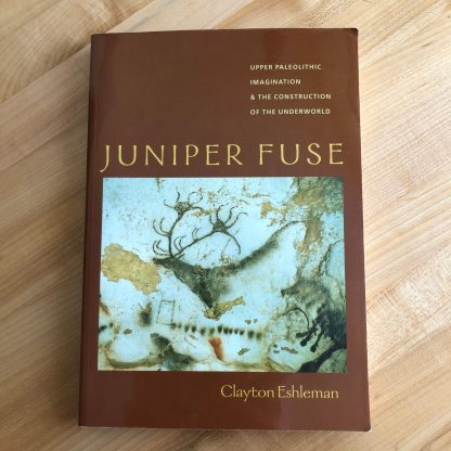 Juniper Fuse by Clayton Eshleman in paperback, lying on a maple tabletop. The brown bookcover features tan typography and a photo of a paleolithic cave painting.