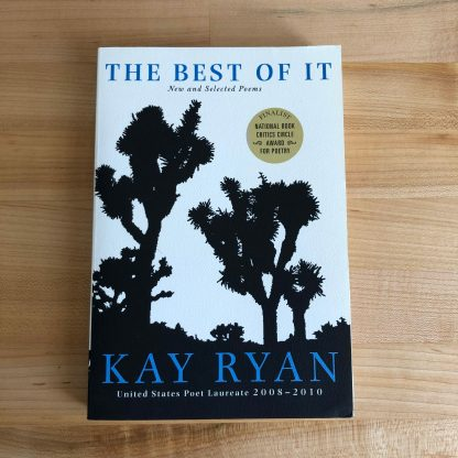 The Best of It in paperback, lying on a maple tabletop. The white book cover features black silhouetted cactus shapes and and blue lettering. A gold seal in the upper right indicates the book's award-winning status.
