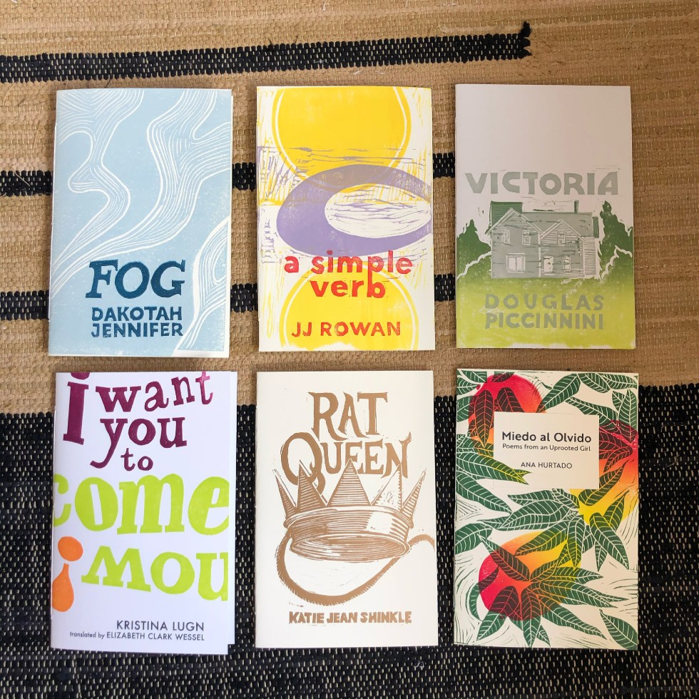 Six handmade chapbooks with hand-printed linocut covers are arranged in a three-by-three grid on a woven rug. They are Fog by Dakotah Jennifer, a simple verb by JJ Rowan, Victoria by Douglas Piccinnini, I Want You to Come Now! by Kristina Lugn translated by Elizabeth Clark Wessel, Rat Queen by Katie Jean Shinkle, and Miedo al Olvido: Poems from an Uprooted Girl by Ana Hurtado.