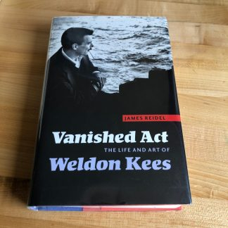 Vanished Act: The Art and Life of Weldon Kees in hardcover, lying on a maple tabletop. The jacket features a black and white photo of the poet with water in the background.