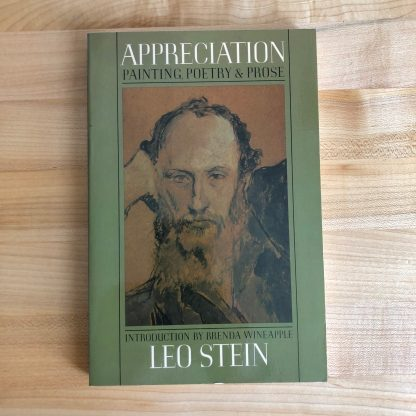 A copy of Appreciation by Leo Stein in paperback, lying on a maple tabletop. The paperback is olive green with a painting of Leo Stein by Pablo Picasso the center, framed by the title and some narrow black lines.