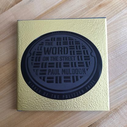 The Word on the Street in harddover, lying on a maple tabletop. The gold metallic jacket is textured and features a black manhole cover design with the title and author's name embossed in raised letters.