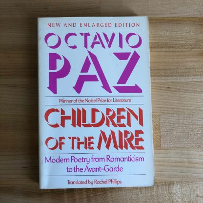 The Children of the Lyre by Octavio Paz. The white paperback has pink and orange lettering. It lies flat on a maple tabletop.