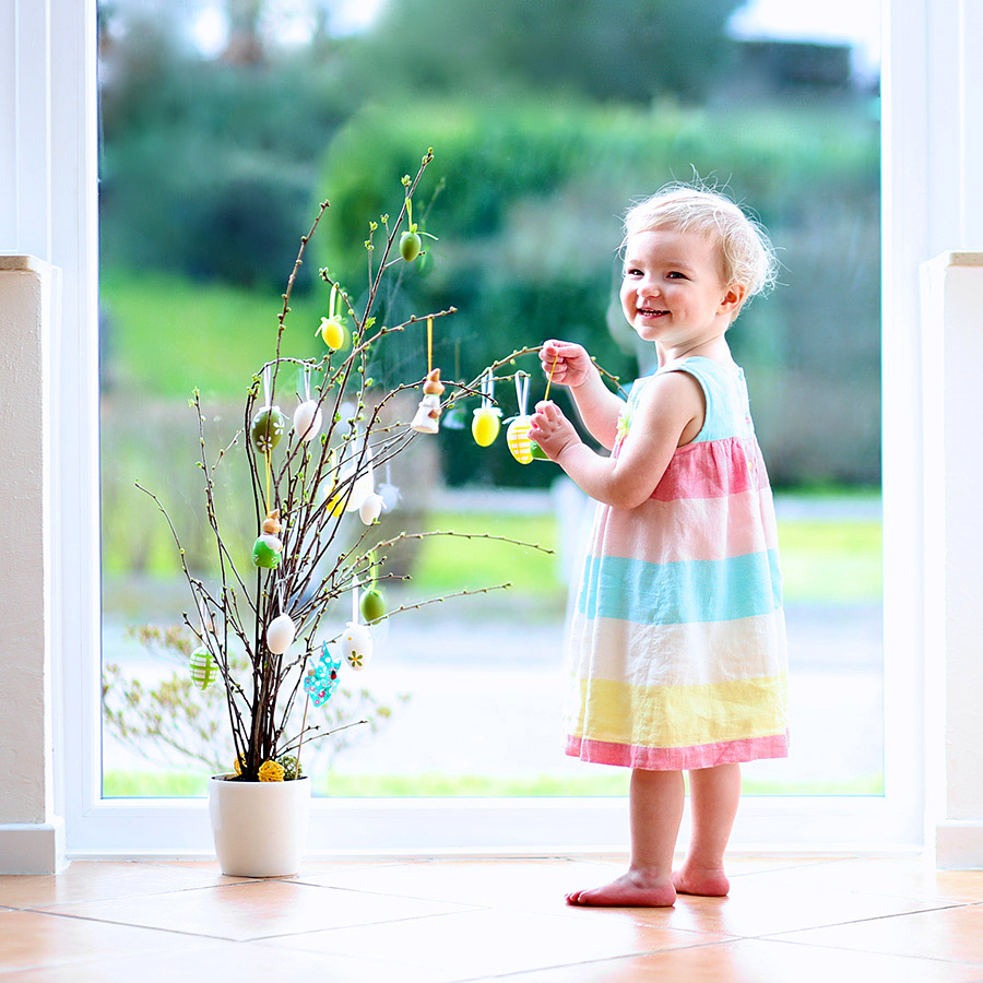 child decorating an Easter tree