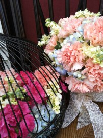 Bouquet next to a bird cage filled with flowers.
