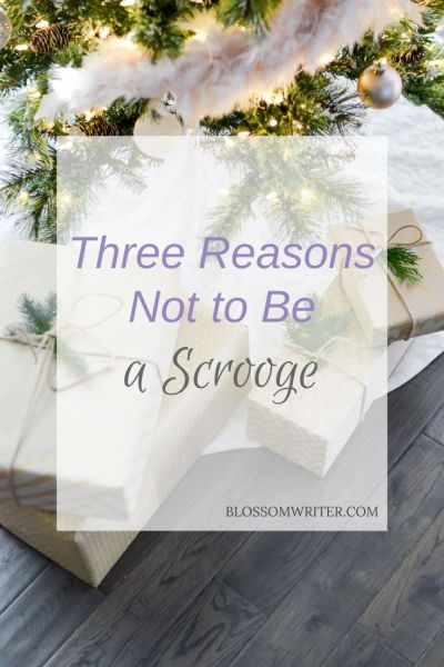 "Wrapped presents under a Christmas tree with white lights. Text reads, ""Three Reasons Not to Be a Scrooge."""