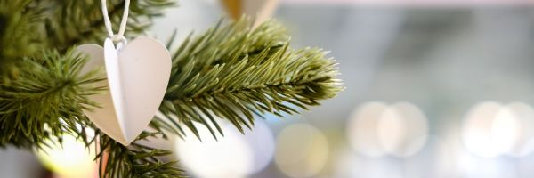 An image of a Christmas tree branch with a wooden heart ornament.