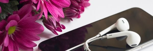 A picture of white earphones laying on top of a smartphone with pink daisy in the left corner.