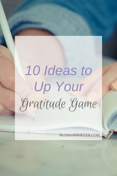 "A close-up image of someone writing in a journal. Text reads, ""10 Ideas to Up Your Gratitude Game."""