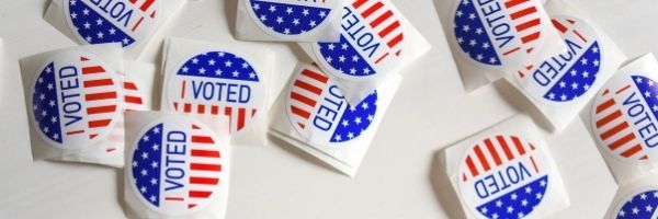 """An image of """"I Voted"""" stickers scattered on a white table."""