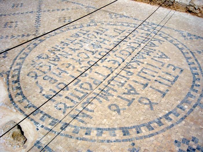 A Greek inscription, in tile mosaic, on the street.