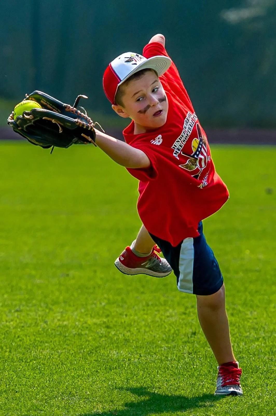 Boy Plays At Amputee Softball Team Kids Camp