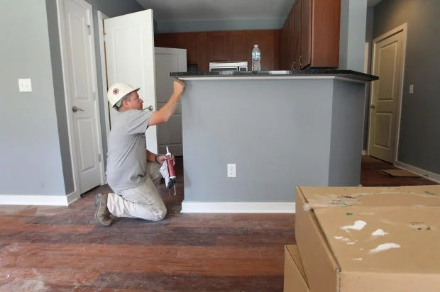 Kevin Banel Left With Bokal Commercial Construction Caulks Some Trim Around The Countertop In A Kitchen Of An Apartment Located 3439