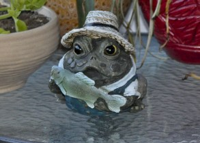 Close up of Frog statute holding a fish.g