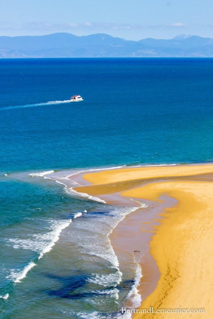 Bateau au large et plage de la baie de Sandfly