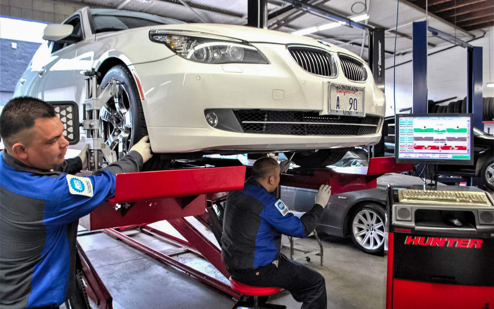 Certified mechanics performing a wheel alignment