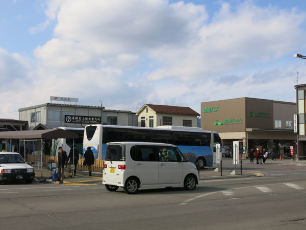 Takayama station (left / white building) and Nohi bus Takayama Bust Terminal (right / Brown and green sign)