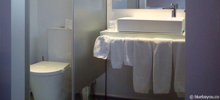 Bad aus Glas im Hotelzimmer in Viana do Castelo (Portugal): Blick vom Bett auf die Toilette.