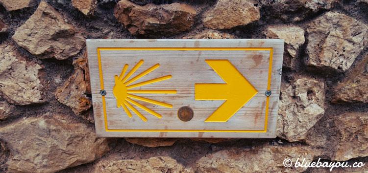 Schild auf dem Jakobsweg mit der Muschel, die nach Santiago de Compostela zeigt.