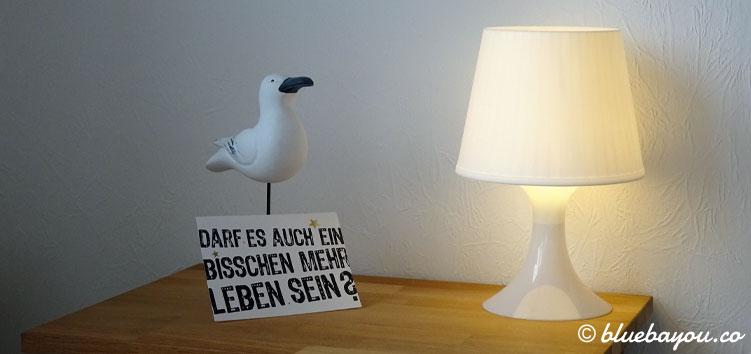 Der Nachttisch meiner Ferienwohnung in Schleswig-Holstein mit Vogel-Deko und Postkarte.