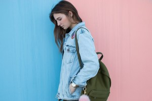 A girl in a denim jacket in front of a pink and blue wall.