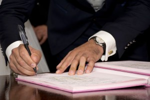 A man in a suit signing a moving contract.