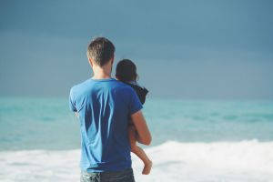A parent holding a child by the sea and talking to it.