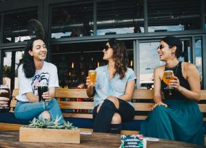 Three women sitting on a bench laughing