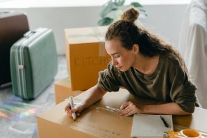 A woman packing and labeling moving boxes