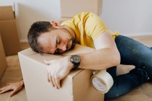 a man in a yellow t-shirt sleeping on a moving box